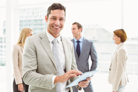 work suit: Portrait of businessman using digital tablet with colleagues behind in office