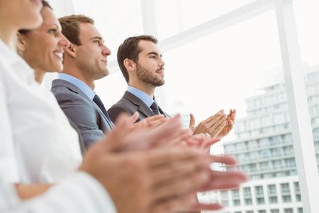 manos aplaudiendo: Los j�venes empresarios que aplauden las manos en la oficina Foto de archivo