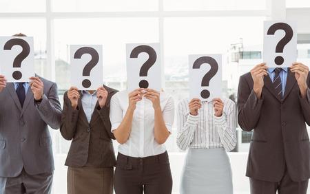 signo de interrogaci�n: La gente de negocios la celebraci�n de signos signo de interrogaci�n delante de sus rostros en la oficina Foto de archivo