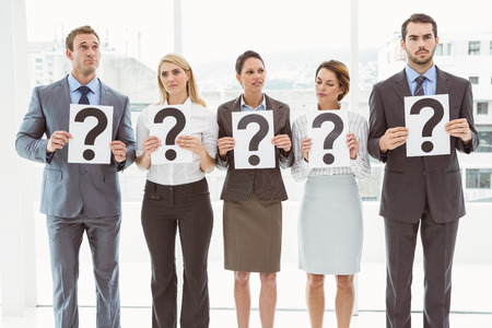 Business people holding question mark signs in office photo