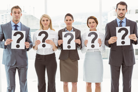 Portrait of business people holding question mark signs in office photo