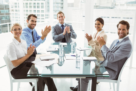 Young business people clapping hands in board room meeting at office