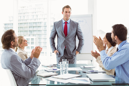 Young business people clapping hands in board room meeting at office photo