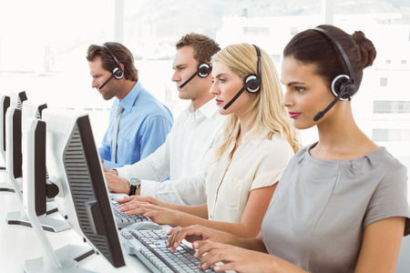 Side view of young business people with headsets using computers in office photo