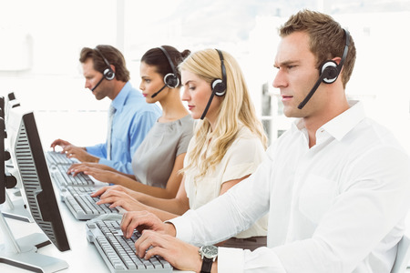 center agent: Side view of young business people with headsets using computers in office