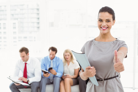 classy woman: Businesswoman gesturing thumbs up against people waiting for job interview in office