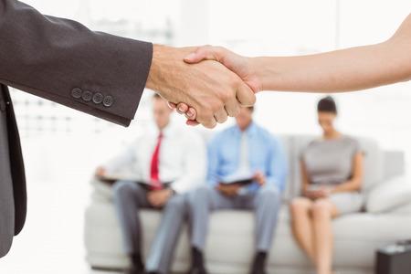 Handdruk naast mensen die wachten op sollicitatiegesprek in het kantoor Stockfoto