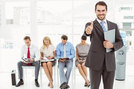 Businessman gesturing thumbs up against people waiting for job interview in office