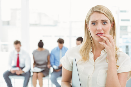 Portrait of businesswoman against people waiting for job interview in office