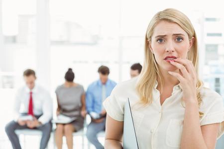 Portret van zakenvrouw tegen mensen die wachten op sollicitatiegesprek in het kantoor