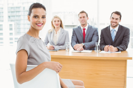 reviewer: Portrait of woman sitting in front of corporate personnel officers in office