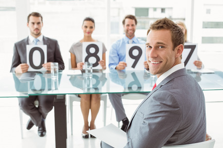 Smiling interview panel holding score cards in bright office photo