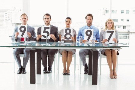 Interview panel holding score cards in bright office photo
