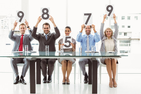 Portrait of interview panel holding score cards in bright office photo