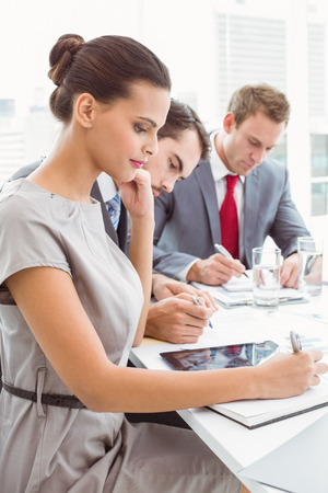 young business people: Young business people writing notes in board room meeting at office