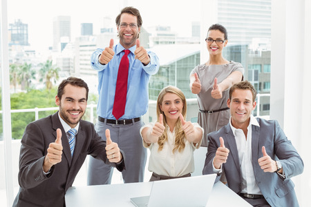sit up: Portrait of confident happy business people gesturing thumbs up in office Stock Photo