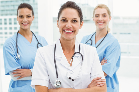 Portrait of confident female doctors with arms crossed at medical office photo