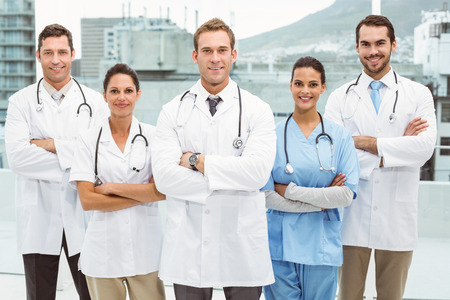 Portrait of confident doctors with arms crossed at medical office photo