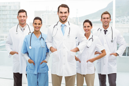 Portrait of confident doctors with hands in pockets at medical office photo