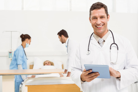 Male doctor using digital tablet with colleagues and patient behind photo