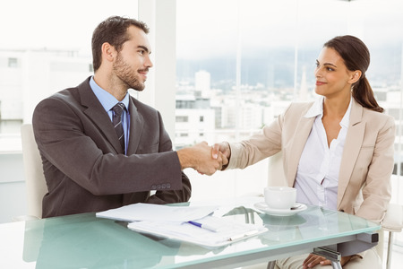 Two young executives shaking hands in the office photo