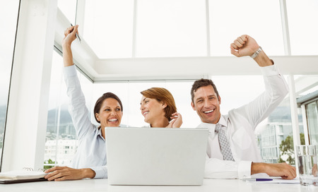Cheerful business people cheering in front of laptop at office desk photo