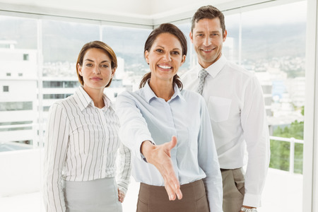 Portrait of beautiful young businesswoman with colleagues offering handshake at office photo