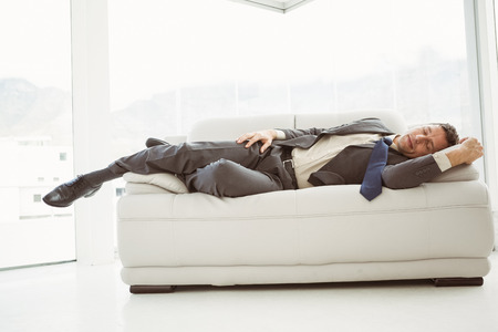 sleeping room: Full length of a young businessman sleeping on couch in living room