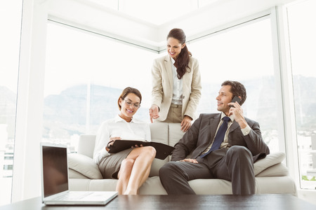 Three young business people in discussion in the living room photo