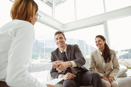 Couple in meeting with a female financial adviser at home Stockfoto