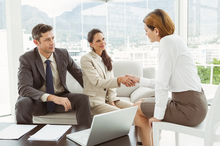 advisor: Couple in meeting with a female financial adviser at home Stock Photo