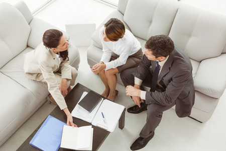 Couple in meeting with a female financial adviser at home Foto de archivo