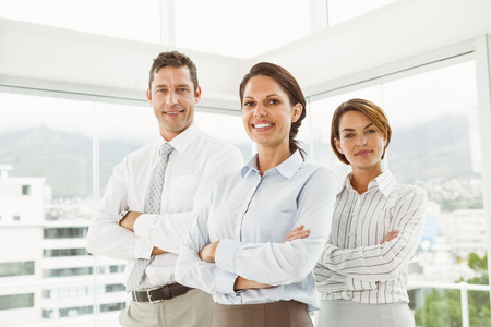 Portrait of confident young business people with arms crossed in office photo