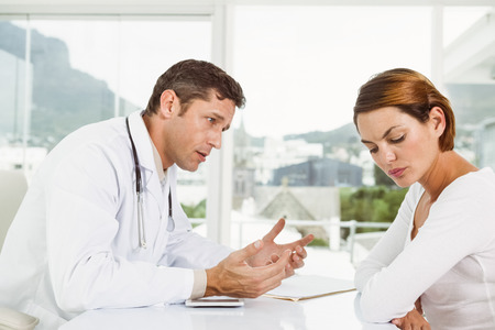 Male doctor in discussion with patient at desk in medical office photo