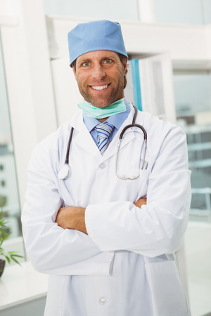 Portrait of smiling male doctor with arms crossed in medical office photo
