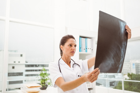 Serious female doctor examining x-ray in the medical office photo