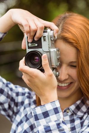 Pretty redhead taking a picture with retro camera in the park photo