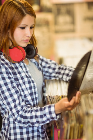 record shop: Redhead with a headphone around the neck holding a vinyl in the store