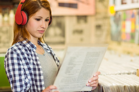 Girl looking for vinyl while listening to music in the store photo