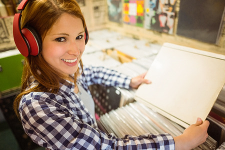 record shop: Pretty redhead searching a vinyl and smiling at camera in the store