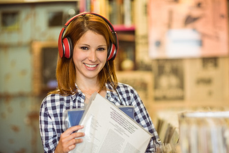 record shop: Smiling woman listening music and holding vinyls in the store