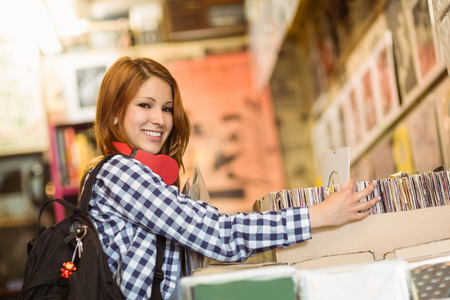 Pretty redhead searching a vinyl and smiling at camera in the store photo