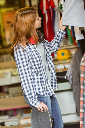 thrift store: Girl looking at clothes while holding her skateboard in the store