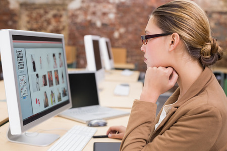 computer monitor: Side view of young businesswoman using computer at office desk Stock Photo