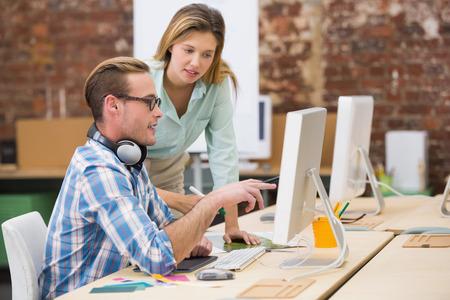 ležérní: Boční pohled na koncentrovaných příležitostné fotografických editorů pomocí počítače v kanceláři Reklamní fotografie