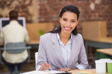 Portrait of smiling young businesswoman writing diary in the office photo