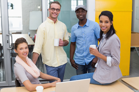 Group of young colleagues with coffee cups during break at office photo