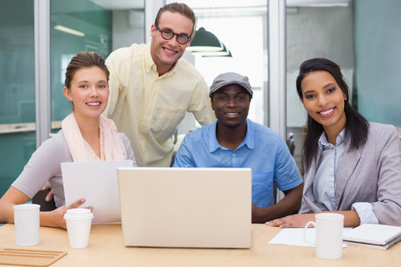 Group of young colleagues using laptop at office photo