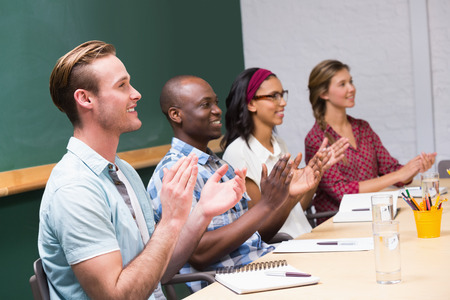 manos aplaudiendo: Los j�venes empresarios que aplauden las manos en reuni�n en la oficina