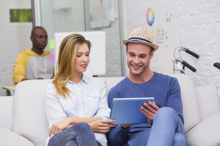 Young casual business people using digital tablet on couch in the office photo